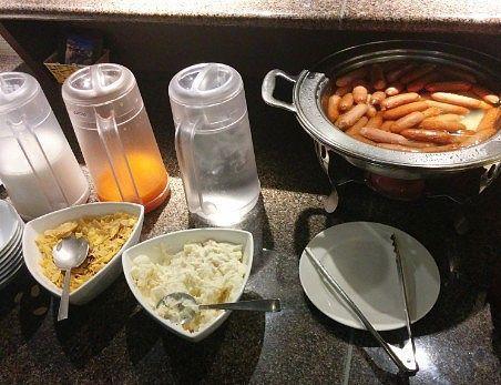 ウインナーとポテトサラダ、シリアルに牛乳とオレンジジュース