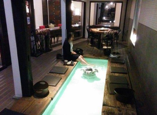 足湯カフェの足湯に浸かってる女性