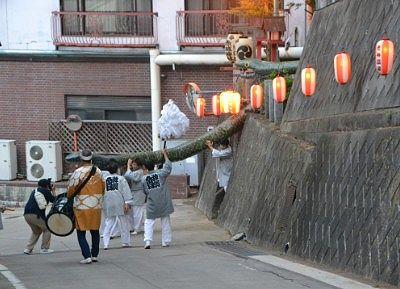 神社の石段を下りてきた大蛇神輿と担ぎ手たち