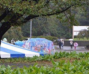 小雨の中かかし祭りに来た家族連れ