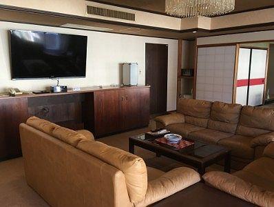 応接室のソファーと大型の壁掛けテレビの様子