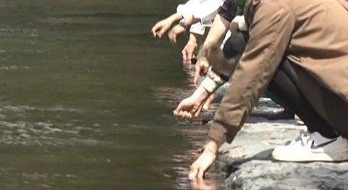 五十鈴川で手を清める様子