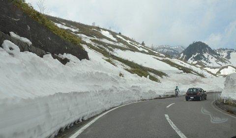 雪の回廊をドライブする車と自転車