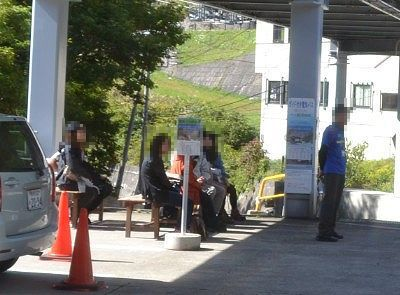 バス停で電気バスを待つベンチと観光客
